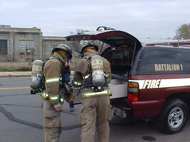 Two fire fighters in full gear plan their next move.